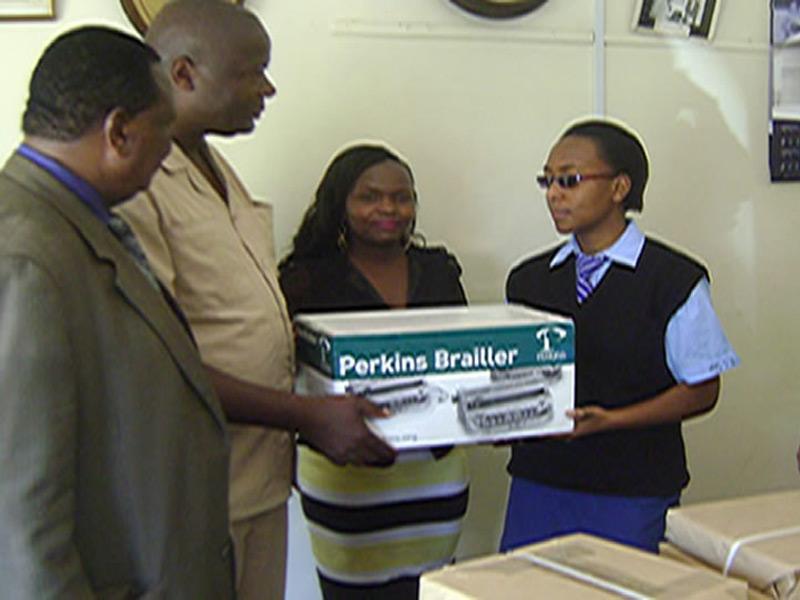 Students receiving braille machine